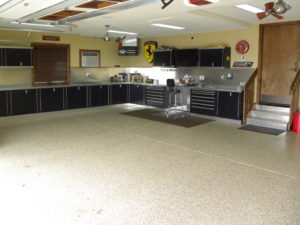 global garage flooring remodel with black and stainless cabinets
